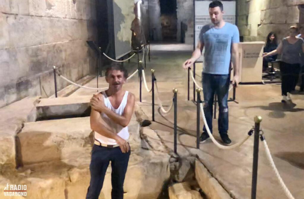 En af de lokale vasker sig i ønskebrønden og går amok, da vagten (til højre) siger til ham, at han ikke må.