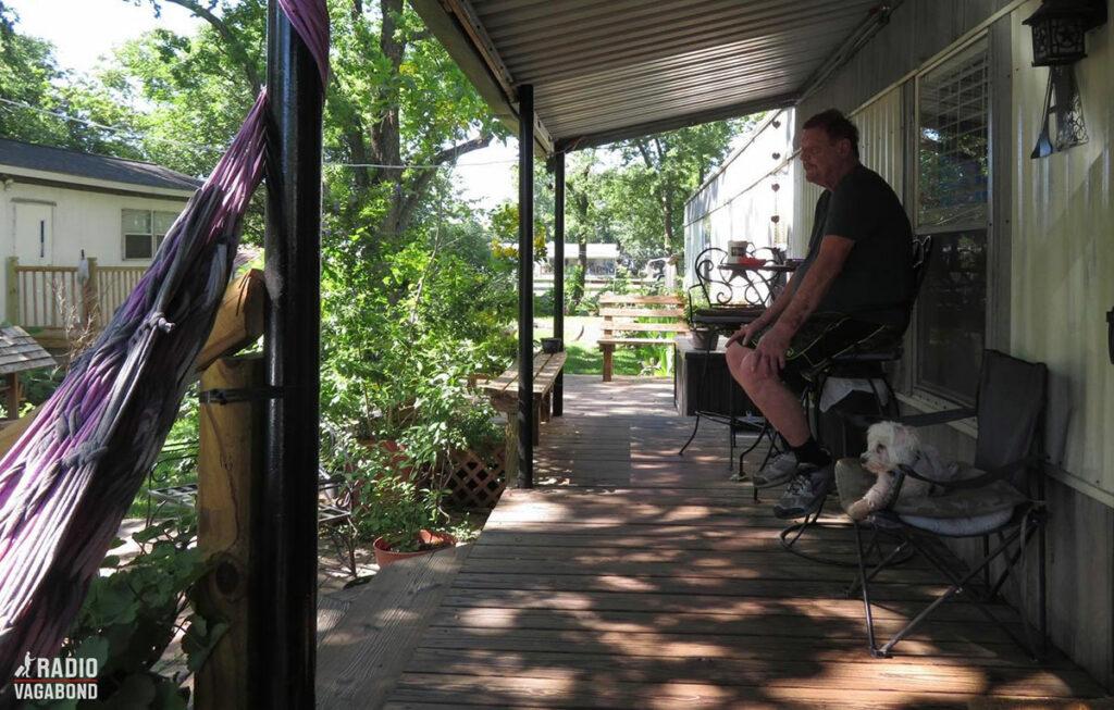 Mens solen langsomt går ned, begynder det at regne, og jeg satte mig ned med Ed på deres veranda foran traileren